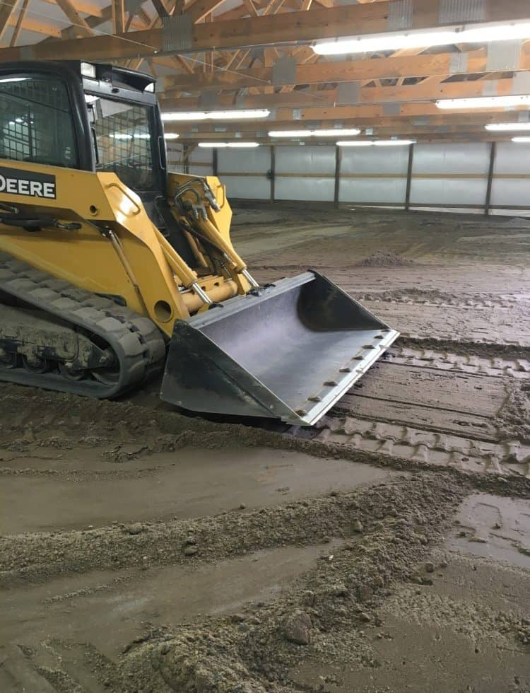 Tractor preparing riding surface for horse arena
