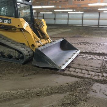 Tractor leveling riding surface of horse arena